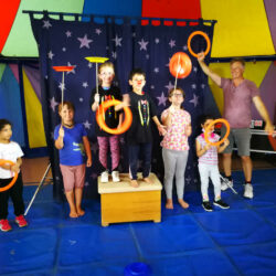 Kinder posieren mit Michael Behrens im Zirkuszelt
